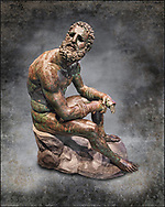 Rare original Greek bronze statue of an Athlete after a boxing match, a 1st cent BC. The athlete, seated on a boulder, is resting after a boxing match. The boulder is a modern addition that replicates the ancient original. The face, ears, and nose are severely wounded by blows received during the match. No wounds appear on the body since ancient boxing practices made the afce the main target. The boxer is only wearing a sort of loin cloth (kynodesme) around his waist. Elaborate leather gloves (himantes oxeis) protect the hands and the forearms. They consist of thick leather straps that bind the four fingers, leaving the thumb free. On the forearms the gloves are bordered with fur lining. A series of marks on the straps above the left ring fingers seem to be a signature of the Athenian sculptor Appolonios, son of Nestor who was active during the 1st century B.C. Careful analysis shows that the marks are actually corrosions of the bronze surface. The Greek letter 'a' is impressed on the middle toe of the left foot and is probably a mark identifying the workshop that produced the statue. The statue of the boxer is of the highest quality with a highly detailed rendition of the athletic anatomy and facial feature. The artist was clearly inspired by the style of Greek sculptor Lysippus and scholars generally consider it an original Greek bronze of the 1st Century B.C. . The National Roman Museum, Rome, Italy. Photo wall art print by  Photographer Paul E Williams