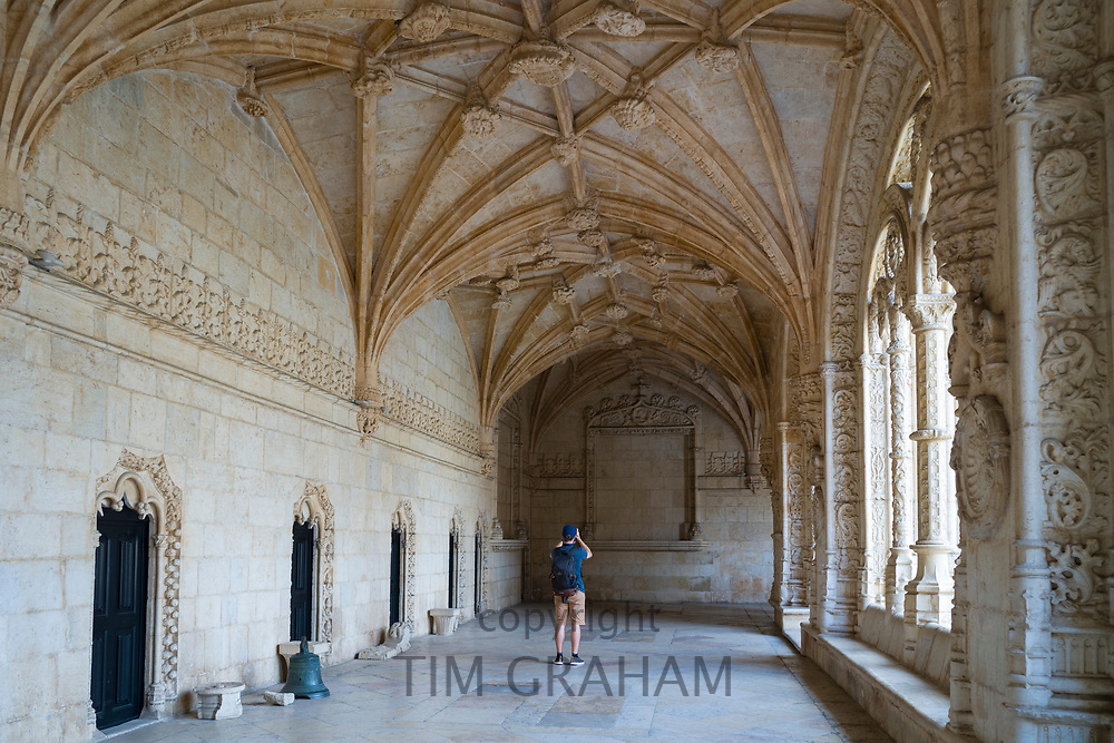 Tourist taking photographs in cloisters of famous Monastery of Jeronimos - Mosteiro  dos Jeronimos in Lisbon, Portugal