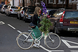 © Licensed to London News Pictures. 26/09/2021. London, UK. A woman on a bike carry exhibitors' plants on the last day of the 2021 Chelsea Flower show. A wide array of unusual and striking display items can be purchased on the closing day of The Royal Horticultural Society flagship flower show, held at the Royal Hospital in Chelsea since 1913. Photo credit: Ben Cawthra/LNP