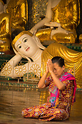 Woman praying in front of a reclining Buddha at the Shwedagon Pagoda complex. situated on Singuttara Hill in the center of Yangon (Rangoon)