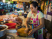 14 DECEMBER 2015 - BANGKOK, THAILAND:  A vendor washes the cutting board in her chicken shop in Bang Chak Market. The market closes permanently on Dec 31, 2015. The Bang Chak Market serves the community around Sois 91-97 on Sukhumvit Road in the Bangkok suburbs. About half of the market has been torn down. Bangkok city authorities put up notices in late November that the market would be closed by January 1, 2016 and redevelopment would start shortly after that. Market vendors said condominiums are being built on the land.      PHOTO BY JACK KURTZ