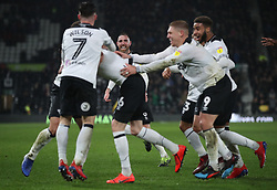 Derby County captain Richard Keogh (distant rear) on his 600th game watches Derby County's Scott Malone and teammates celebrate the winning goal against Wigan Athletic,