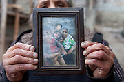 """The daughter of Jan Ondic - who is one of the oldest inhabitants at the Roma settlement - holding a frame with a photograph of her beloved mother. She lives with her family at the Roma part of the district """"Podsadek"""". The town of Stara Lubovna has a population of 16350, of whom 2 060 (13%) are of Roma origin. The majority of Roma live in the Podsadek district, where 980 (74%) out of 1330 inhabitants are Roma."""