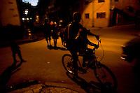 Cuban boys ride through streets at night.