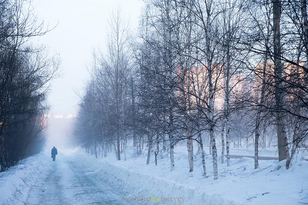 Man walking through winter landscape, Tynda, Amur region, Siberia, Russia