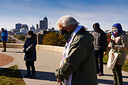 "18 OCTOBER 2020 - DES MOINES, IOWA: A person bows their head during 8 minutes and 46 seconds of silence at ""Shattering the Silence"" on the grounds of the Iowa Judicial Branch, with the Des Moines city skyline in the background. About 100 people gathered on the grounds of the Iowa Judicial Building in Des Moines to ""shatter the silence"" on racism. The event, Shattering the Silence, was designed to call on white people and especially white people of faith to do racial justice work and to no longer remain silent.          PHOTO BY JACK KURTZ"