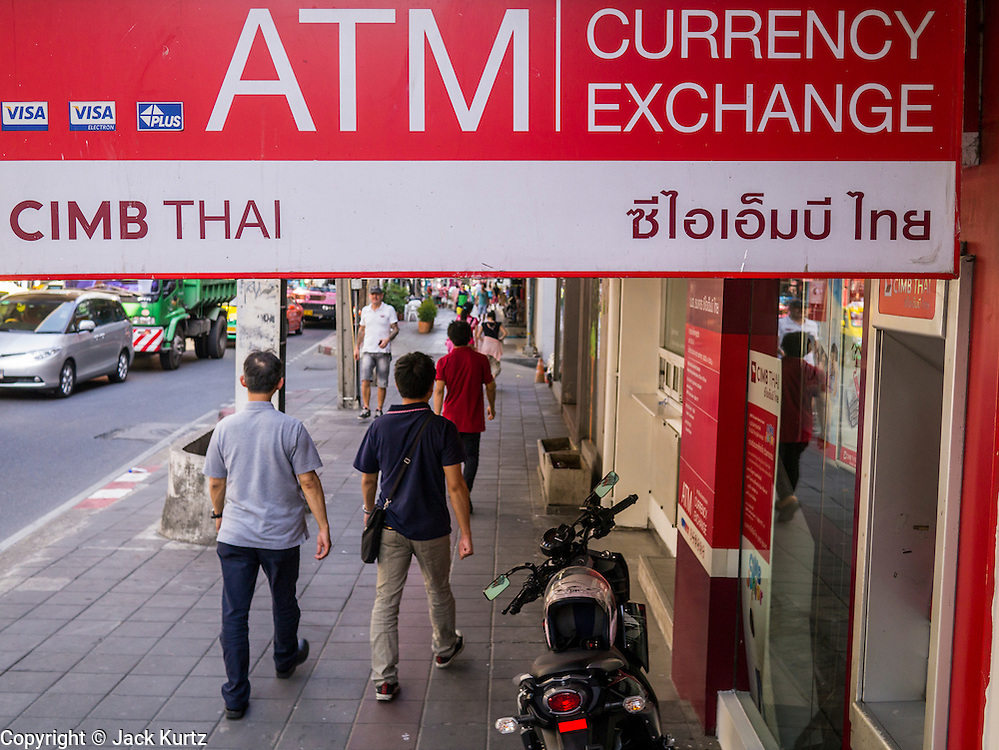 22 APRIL 2013 - BANGKOK, THAILAND: People walk past a foreign currency exchange on a Bangkok street. The Thai Baht has gained markedly against the US Dollar, the Euro and Pound Sterling in recent months. On Monday, the Baht was trading at 28.57 Baht to 1 US Dollar on Apr. 22. The strengthening Baht means imported goods are cheaper in Thailand, but Thai exports cost more in other countries. It also means tourists and expats who live in Thailand have less money to spend as their currencies buy fewer Baht. The baht has risen 5 percent against the dollar this year to its highest level since before the Asian financial crisis in 1997. The Federation of Thai Industries, which has led calls for the authorities to act to lower the baht, said the rise in the past two weeks had been too rapid and its members were finding it hard to cope with the volatility because as the Baht appreciates their exports become more expensive. Thailand is among the world's leading exporters of rice, chicken, pork, electrical components, cars and is the leading exporter of canned tuna.    PHOTO BY JACK KURTZ