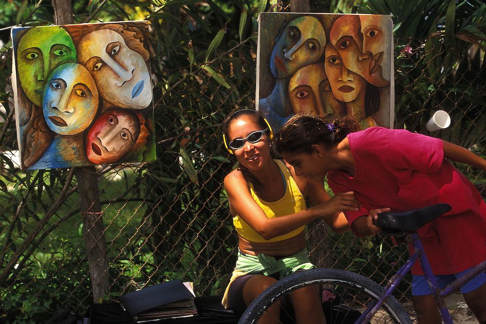 BELIZE / San Pedro / Street painter showing her work of art...© JOAN COSTA