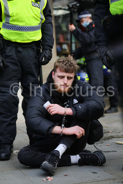 Kill the Bill demonstration in Central London against the proposed Police, Crime, Sentencing and Courts Bill on the 3rd April 2021, London, United Kingdom. A young protester sites arrested behind police lines. It is not know why he was arrested. After the protest ended in Parliament Square police cleared the streets, arresting several in the process. Thousands turned out in London and across the UK to show their objection to the Governments proposed bill. Many fear the bill is meant to suppress acts of protesting and demonstrations. The police will be given greater powers to prevent and stop actions of civil disobedience and peaceful protests and many see this as a suppression of their civil liberties. Sentencing for acts of peaceful protest is also likely to be much harsher and that may also act as a deterrent to protest.