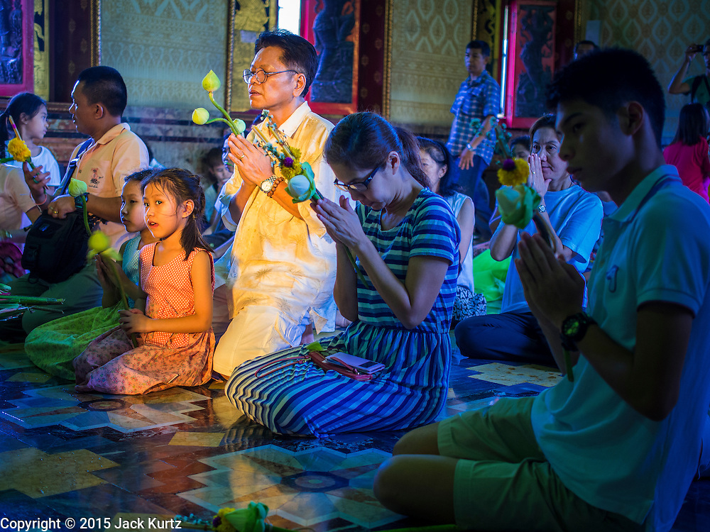 """04 MARCH 2015 - BANGKOK, THAILAND: People pray in the """"wiharn"""" or prayer hall at Wat Benchamabophit on Makha Bucha Day. Makha Bucha Day is an important Buddhist holy day and public holiday in Thailand, Cambodia, Laos, and Myanmar. Many people go to temples to perform merit-making activities on Makha Bucha Day. Wat Benchamabophit is one of the most popular Buddhist temples in Bangkok.    PHOTO BY JACK KURTZ"""