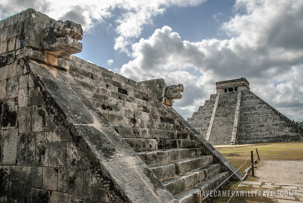 In the background at right is the Temple of Kukulkan (El Castillo) and at left in the foreground are the carved jaguar heads of the Venus Platform at Chichen Itza Archeological Zone, ruins of a major Maya civilization city in the heart of Mexico's Yucatan Peninsula.