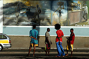 Youth of Mindelo on the road next to a painted mural. The historical zone of Mindelo owns several examples of colonial architecture.