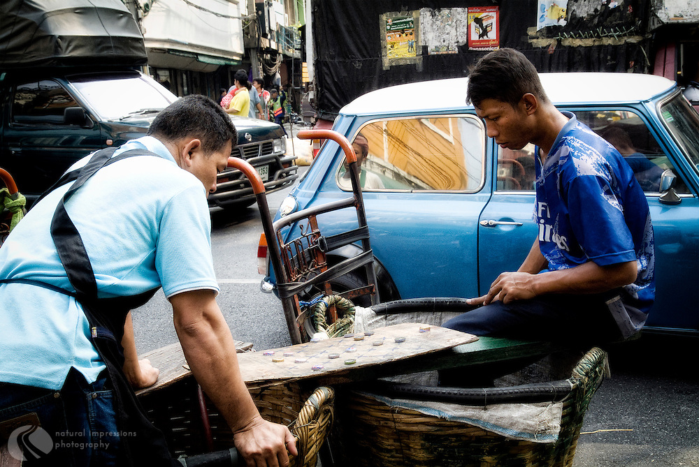 Always time for a game, street merchants pause in their day