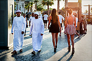 Arab men pass sex workers on Jumeirah Beach, a white sand beach, restaurant, and hotel boardwalk in Dubai in the United Arab Emirates.  © Steve Raymer / National Geographic Creative