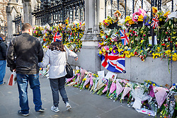© Licensed to London News Pictures. 27/03/2017. London, UK. Members of public pay respects to the victims of Westminster terror attack outside the Houses of Parliament in London on Monday, 27 March 2017. Photo credit: Tolga Akmen/LNP