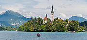 A rowboat approaches the medieval church on glacially formed Lake Bled (Slovene: Blejsko jezero) in the Julian Alps in northwestern Slovenia, Europe. The lake surrounds Bled Island (Blejski otok, the only natural island in Slovenia), upon which stands the Pilgrimage Church of the Assumption of Mary (Slovenian: Cerkev Marijinega vnebovzetja), built in the 15th century and now popular for romantic weddings. Lake Bled hosted the World Rowing Championships in 1966, 1979, 1989, and 2011. The lake is 35 kilometers from Ljubljana International Airport. Panorama stitched from 2 overlapping photos.