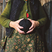 A peasant women wearing a traditional sheepskin waistcoat and flowery apron holds a ball of black wool, Botiza, Maramures, Romania. Traditionally subsistence farmers in Maramures raise their own sheep to provide wool for knitting and weaving clothing.