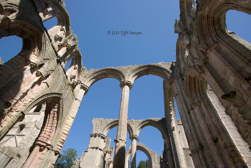 Yorkshire, Fountains Abbey ruins; looking up at bare ruined choirs and empty arches against a plain blue sky.