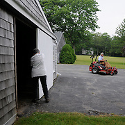 7/3/11 -- Rt 129 , Maine. nancy closes up the shed as Jim rolls up on  his non Deere grass cutter. ..A stretch of the road not often traveled. Spanning communities, classes and styles ~ of farmers and fishermen, retired and plugging, the elite and working waterfront. (This area has huge potential for great photojournalism).  Photo by Roger S. Duncan.