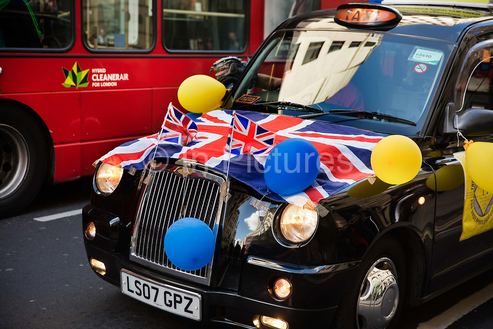 Taxi decked in flags for the Pearly Kings and Queens Harvest Festival celebrations at Guildhall Yard. The annual event features early English entertainment including maypole dancing, Morris dancers and a marching band. The Chelsea pensioners & all the mayors of London take part in this traditional London event.<br /> The London tradition of the Pearly Kings and Queens began in 1875, by Henry Croft. Inspired by the local Costermongers, a close-knit group of market traders who looked after one another and were recognisable by buttons sewed onto their garments, Henry went out on the streets to collect money for charity, wearing a suit covered in pearl buttons to attract attention. When demand for his help became too much, Henry asked the Costermongers for assistance, many of whom became the first Pearly Families. Today, around 30 Pearly Families continue the tradition to raise money for various charities.