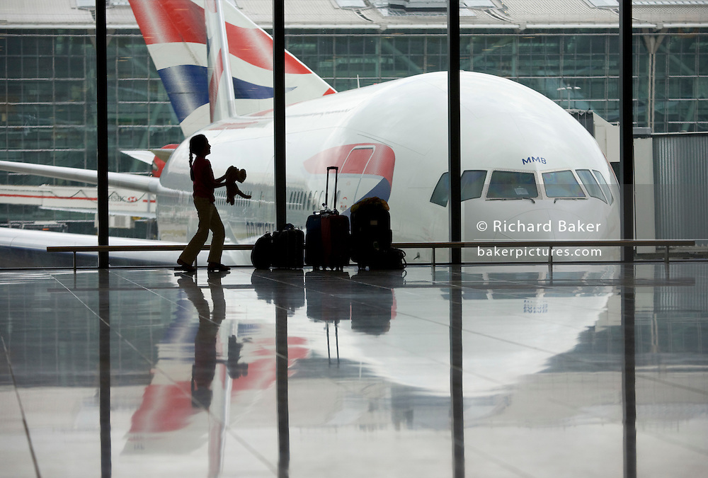 A young girl throws her pet toy tiger in front of a BA 777 airliner in a departure window of Heathrow Airport's T5