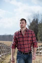 rugged masculine man in a plaid shirt on a ranch
