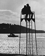 It takes but a little sun to attract a few to Seattle- area beaches. A couple occupied a life-guard tower to watch water traffic at Golden Gardens Park. (Josef Scaylea / The Seattle Times, 1971)