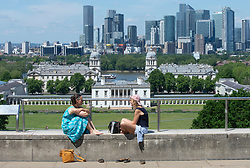 © Licensed to London News Pictures 08/06/2021. Greenwich, UK. Two friends chatting in Greenwich Park, London enjoying the hot sunny weather today. More hot sun is expected at the weekend with hotter temperatures across the UK. Photo credit:Grant Falvey/LNP