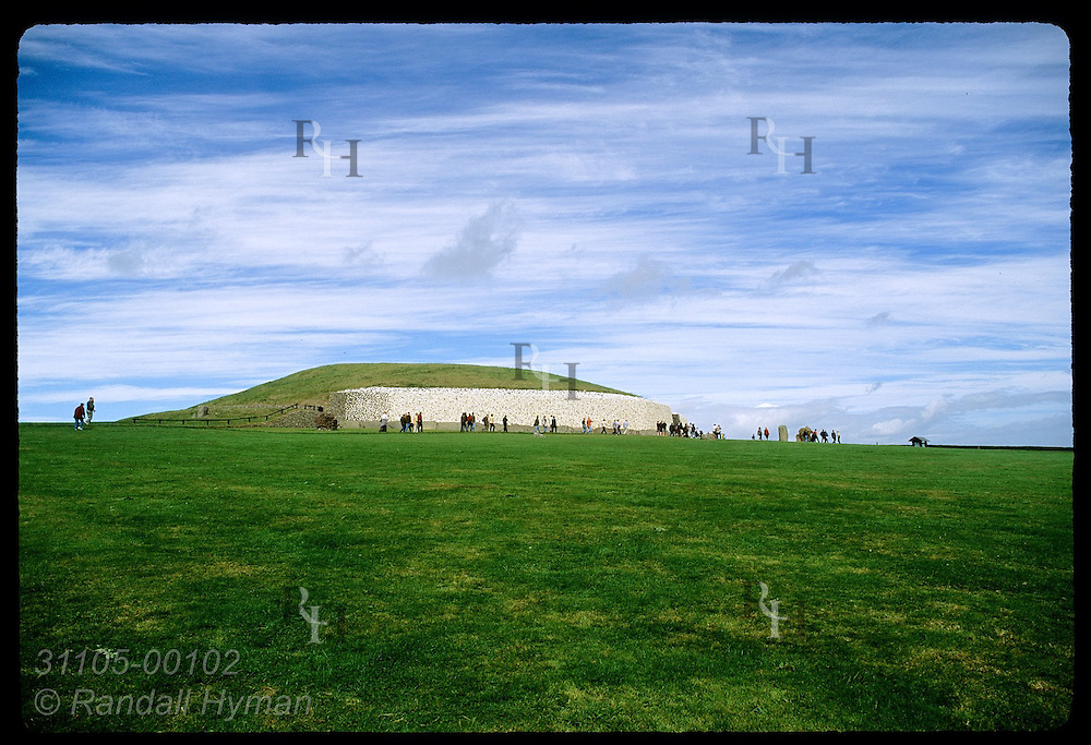 Tourists atop distant ridge visit Newgrange burial mound, a Neolithic (3200 BC) passage grave in Boyne Valley; County Meath, Ireland.