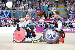 © London News Pictures. 05/09/2012. Captain Steve Brown of the wheelchair rugby GB team passes the ball during the wheelchair rugby opening match. The opening game of the wheelchair rugby competition started today between ParalympicsGB and world champions USA at the Paralympic Games in Stratford, London, UK. Team USA won the match 56 - 44. Photo credit should read Manu Palomeque/LNP