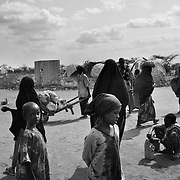 Young children play while the adults bring ration and other supplies outside the Dagahaley refugee camp in the Dadaab refugee camp in northeastern Kenya. Hundreds of thousands of refugees are fleeing lands in Somalia due to severe drought and arriving in what has become the world's largest refugee camp. Photo: Sanjit Das/Panos