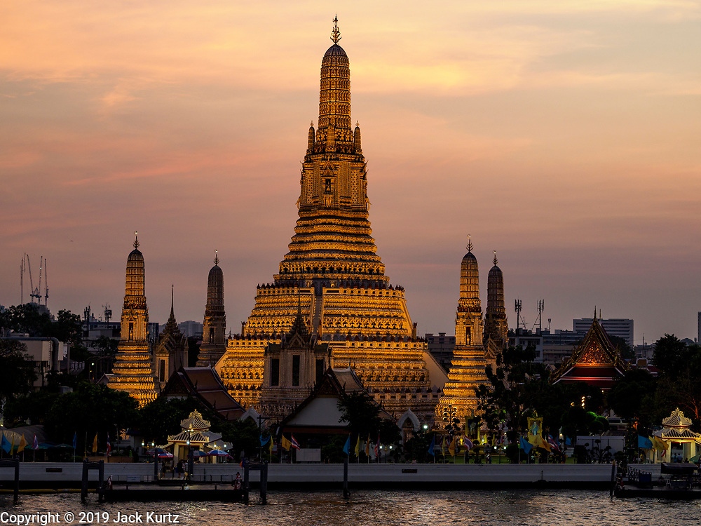 """06 MARCH 2019 - BANGKOK, THAILAND:  The sunsets on Wat Arun. Wat Arun Ratchawararam Ratchawaramahawihan or Wat Arun (""""Temple of Dawn"""") is a Buddhist temple (wat) in Bangkok on the Thonburi side of the Chao Phraya River. The temple derives its name from the Hindu god Aruna, who is personified as the rising sun. Wat Arun is among the best known of Thailand's temples. The temple has existed since at least the seventeenth century, but its distinctive prang (spires) were built in the Khmer style in the early nineteenth century during the reign of King Rama II.   PHOTO BY JACK KURTZ"""