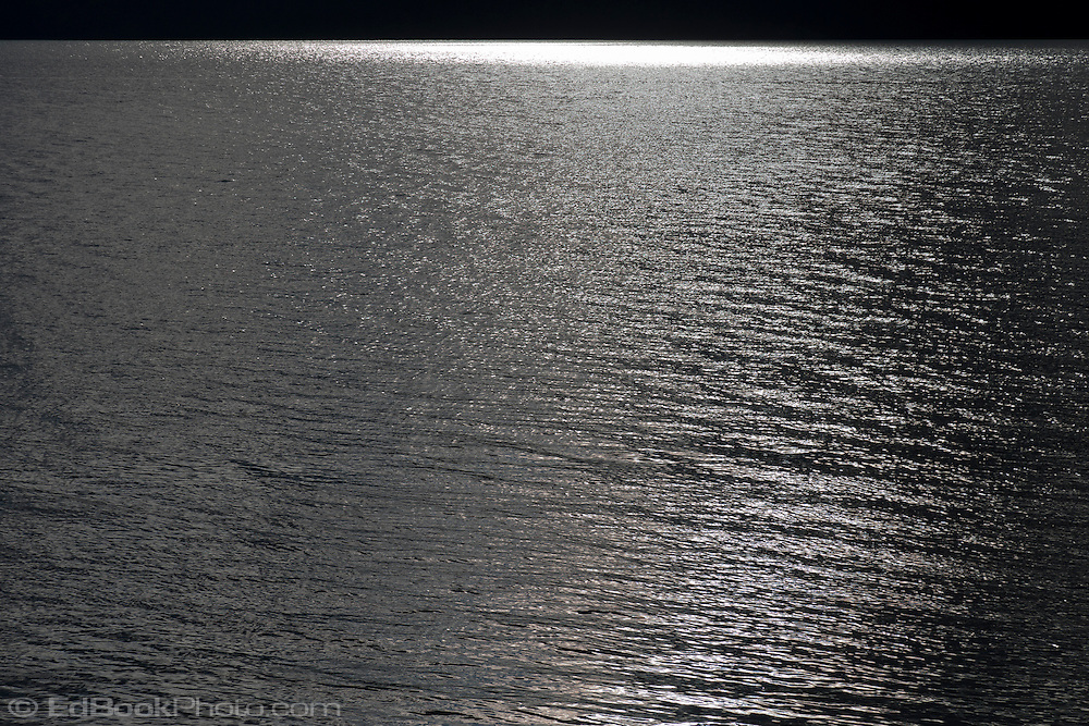 late afternoon sunlight reflects brightly from the Hood Canal of Puget Sound, Washington, USA Viewed looking west from the Kitsap Peninsula to the far shore Olympic Peninsula