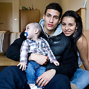 London, UK, December 2011. .Teenage Parents Service at the South London YMCA charity in Lambeth..Carolina with her partner Camillo, 17 years old and their son Jayden, 6 months old..Carolina, 17 years old from Colombia, got pregnant when she was 16. At that time she was really worried to face her parents and about not being able to cope with the baby. When she had the baby she went to live at Teenage Parents Service residence for teenage mothers in Stockwell.