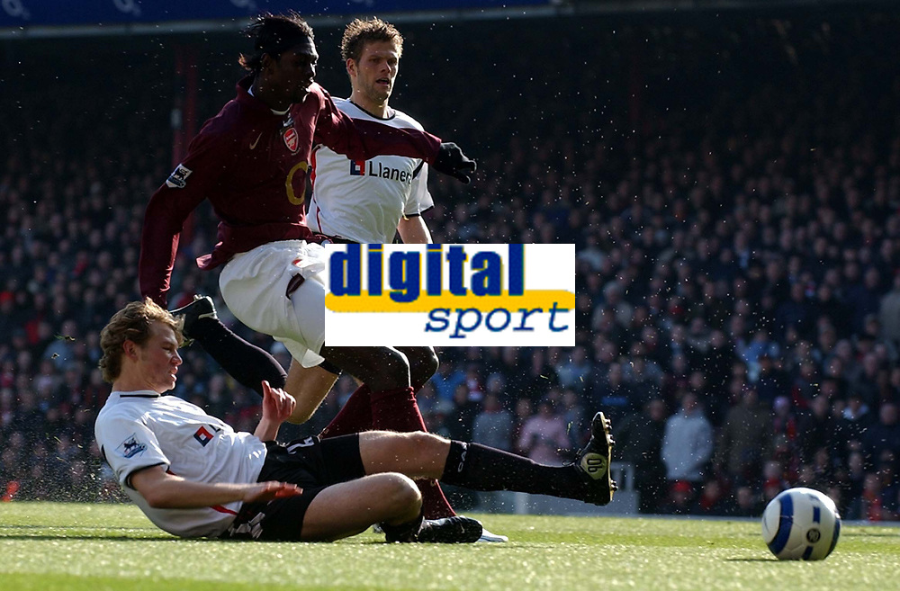 Photo: Olly Greenwood.<br />Arsenal v Charlton Athletic. The Barclays Premiership. 18/03/2006. Arsenal's Emmanuel Adebayor is tackled by Charlton's Jonathan Spector.