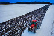A farmer works his land after a fresh early winter snow fall near Denmark, Wisconsin.