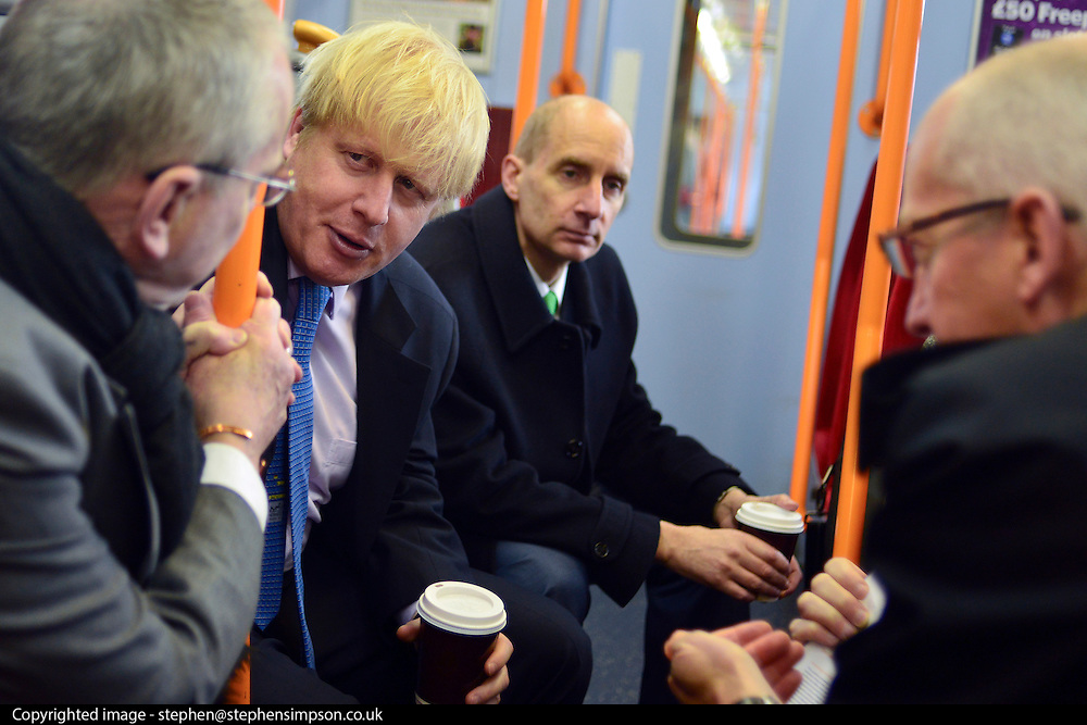© Licensed to London News Pictures. 14/05/2013. London, UK (Left to right) Transport for London's Commissioner, Sir Peter Hendy CBE, Boris Johnson, Lord Adonis, Chairman of the Crossrail 2 Task Force for London First, David Higgins, Network Rail Chief Executive talk on a train back to Waterloo Station in Central London. The Mayor of London, Boris Johnson, leads a short walkabout around Wimbledon High Street to meet local people as he helps launch a public consultation on proposed routes for Crossrail 2. Today 14th May 2013. Photo credit : Stephen Simpson/LNP