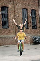 Portrait of teenage couple riding bicycle, smiling