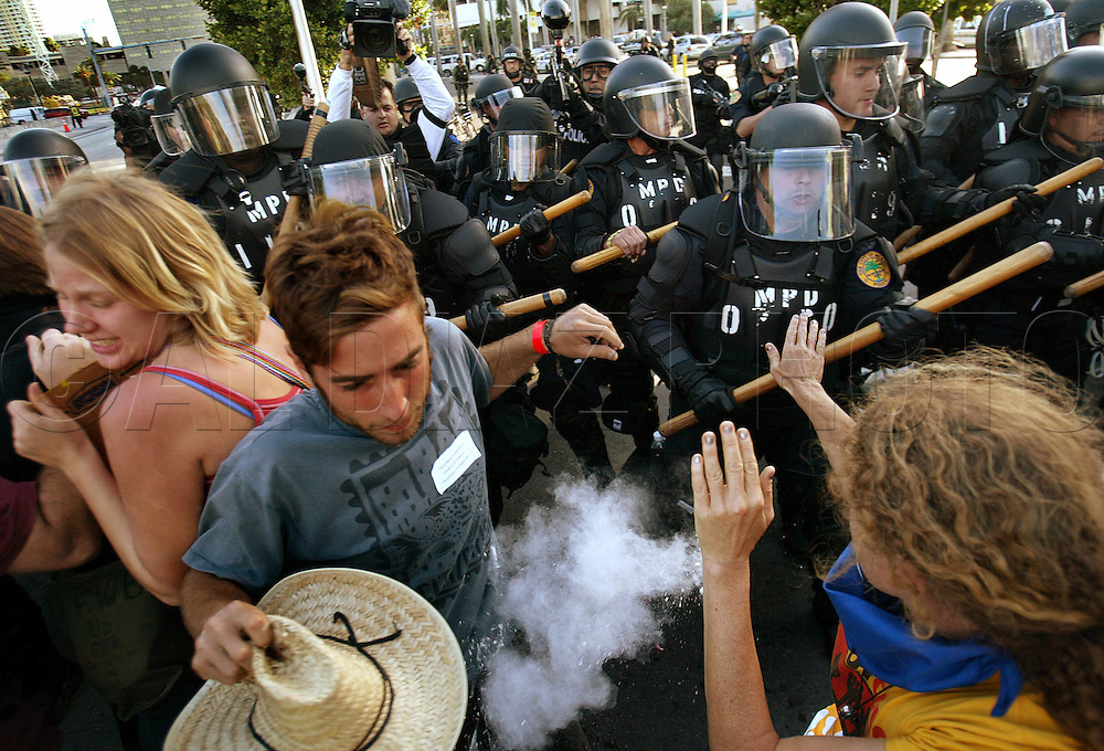 Miami Police officers wearing riot gear advance and fire pepper spray at demonstrators who massed along Biscayne Boulevard protesting the Free Trade Area of the Americas meeting in Miami on October 20, 2003.