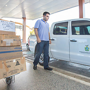 CAPTION: Plastic surgeon Dr Sá (right) and his team arrive at the airport in Manaus, ready to fly to Tabatinga, which lies on Brazil's border with Colombia and Peru. Their supplies are being loaded as the team prepares to begin their journey. LOCATION: Eduardo Gomes International Airport, Manaus, Amazonas, Brazil. INDIVIDUAL(S) PHOTOGRAPHED: Nelson Campos (left) and Dr Álvaro Sá (right).