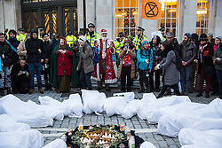 London, UK. 21st December, 2018. Environmental campaigners from Extinction Rebellion remember the 27 people found burnt alive in the Greek village of Mati after July's wildfires during a protest outside Broadcasting House against the lack of coverage by the BBC of the climate change crisis.