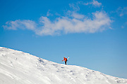 Andy Beeson climbs a snowy slope with skis on his back to catch some turns in the San Juan Mountains, Colorado.