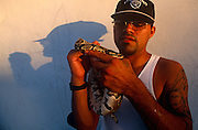 A young man stops to show off his exotic pet python comfortably wrapped aroud his shoulder in Miami, Florida.