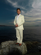 Asian man (40-45) stands in front of Elliott bay and looks into camera.