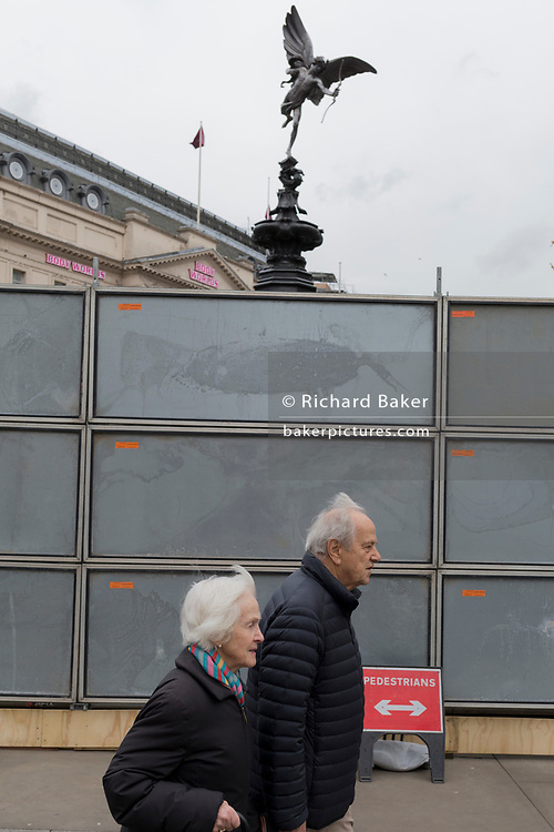 "An elderly couple walk past a temporary construction hoarding beneath the partially hidden statue of the world famous London Victorian-era landmark, Eros in Piccadilly Circus, on 25th February 2020, in London, England. Eros, or the Shaftesbury Memorial Fountain is located at the southeastern side of Piccadilly Circus in London, United Kingdom. Moved after World War II from its original position in the centre, it was erected in 1892–1893 to commemorate the philanthropic works of Lord Shaftesbury, who was a famous Victorian politician and philanthropist. The monument is surmounted by Alfred Gilbert's winged nude statue generally, though mistakenly, known as Eros. This has been called ""London's most famous work of sculpture."""
