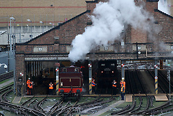 © Licensed to London News Pictures. 13/01/2013, London, UK. Railway workers watch the newly restored Met Locomotive No. 1 steam engine leaves a train depot in London, Sunday, Jan. 13, 2013. The engine will travel through part of the original underground route to mark the 150th anniversary of the opening of the world's first underground in January 1863, and linked to it will be the oldest surviving operational underground carriage, the Metropolitan Railway Jubilee Carriage 353, a set of four Chesham carriages and the world's oldest electric locomotives in service, No 12 Sarah Siddons. Photo credit : Sang Tan/LNP