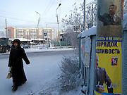 Passantin in der Innenstadt von Jakutsk. Jakutsk wurde 1632 gegruendet und feierte 2007 sein 375 jaehriges Bestehen. Jakutsk ist im Winter eine der kaeltesten Grossstaedte weltweit mit durchschnittlichen Winter Temperaturen von -40.9 Grad Celsius. Die Stadt ist nicht weit entfernt von Oimjakon, dem Kaeltepol der bewohnten Gebiete der Erde.<br /> <br /> Passerby in the city center of Yakutsk. Yakutsk was founded in 1632 and celebrated 2007 the 375th anniversary - billboard announcing the celebration. Yakutsk is a city in the Russian Far East, located about 4 degrees (450 km) below the Arctic Circle. It is the capital of the Sakha (Yakutia) Republic (formerly the Yakut Autonomous Soviet Socialist Republic), Russia and a major port on the Lena River. Yakutsk is one of the coldest cities on earth, with winter temperatures averaging -40.9 degrees Celsius.