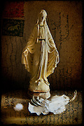 Small statue with white feathers Textured photograph using vintage postcard