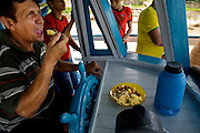 A riverboat captain lunches on rice, beans, spaghetti, potatoes, and pork as he steers upstream from Manacapuru, on the Solimoes River in Brazil. iverboats ply the network of rivers that drain the vast Amazon basin which has very few roads. (From the Book What I Eat: Around the World in 80 Diets.)