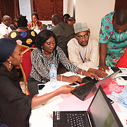 INDIVIDUAL(S) PHOTOGRAPHED: From left to right: Unknown, Vetty Agala, unknown, and unknown. LOCATION: Financing Workshop, Lagos, Nigeria. CAPTION: At the end of the workshop, participants broke into smaller groups to discuss and exchange ideas on how to improve approaches to financing within Nigeria's health care sector.